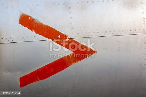 487808089 istock photo Old aircraft aluminum panel with red arrow. 1226371224