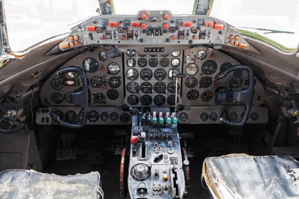 Old aircraft cockpit with steering wheels, control levers, and a lot of gauges stock photo