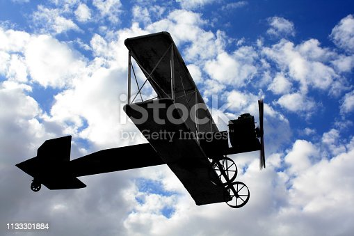 dark gray metal replica of an old bi-wing airplane, flying in front of a beautiful cloudscape on a summer day, showing circular motion with the movement of the propellers