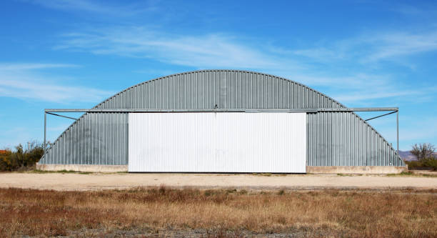 old airport hanger front view of and old sheet metal airport hanger with a white garage door in the desert airplane hangar stock pictures, royalty-free photos & images