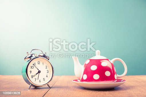 Old alarm clock and teapot with polka dots on table. Retro style filtered photo