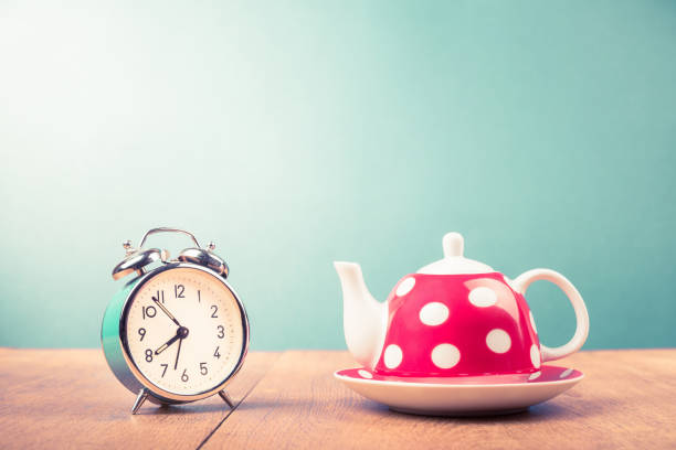 Old alarm clock and teapot with polka dots on table. Retro style filtered photo Old alarm clock and teapot with polka dots on table. Retro style filtered photo early 20th century stock pictures, royalty-free photos & images