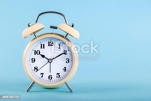 istock Old alarm clock isolated on a blue background with space for text 848765720