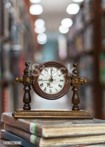 istock Old Alarm clock on stack of book with blur abstract background educational library 1026273030
