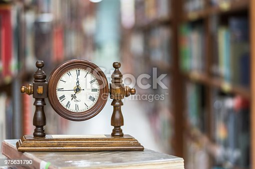istock Old Alarm clock on stack of book with blur abstract background educational library 975631790