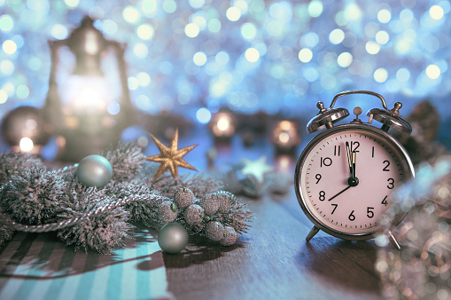 istock Old alarm clock showing five to midnight and glittering decorati 502071208