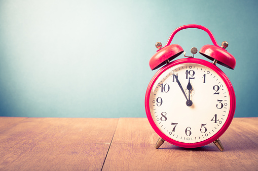 istock Old alarm clock with five minutes to twelve o'clock. Retro style filtered photo 1065761240