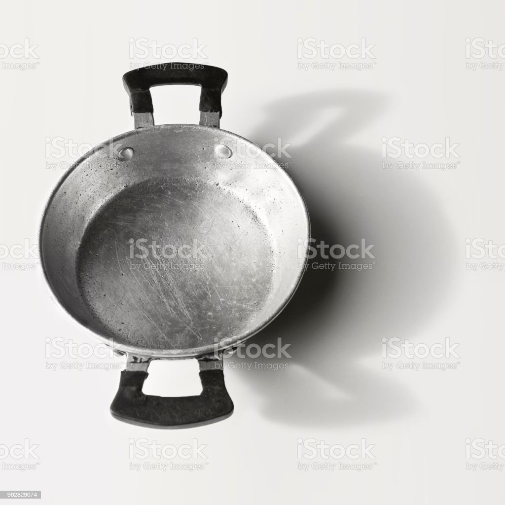 Old aluminum pan seen from above on white background stock photo