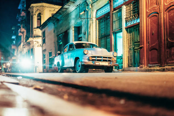 old american car in old havanna street at night - cuba stock photos and pictures