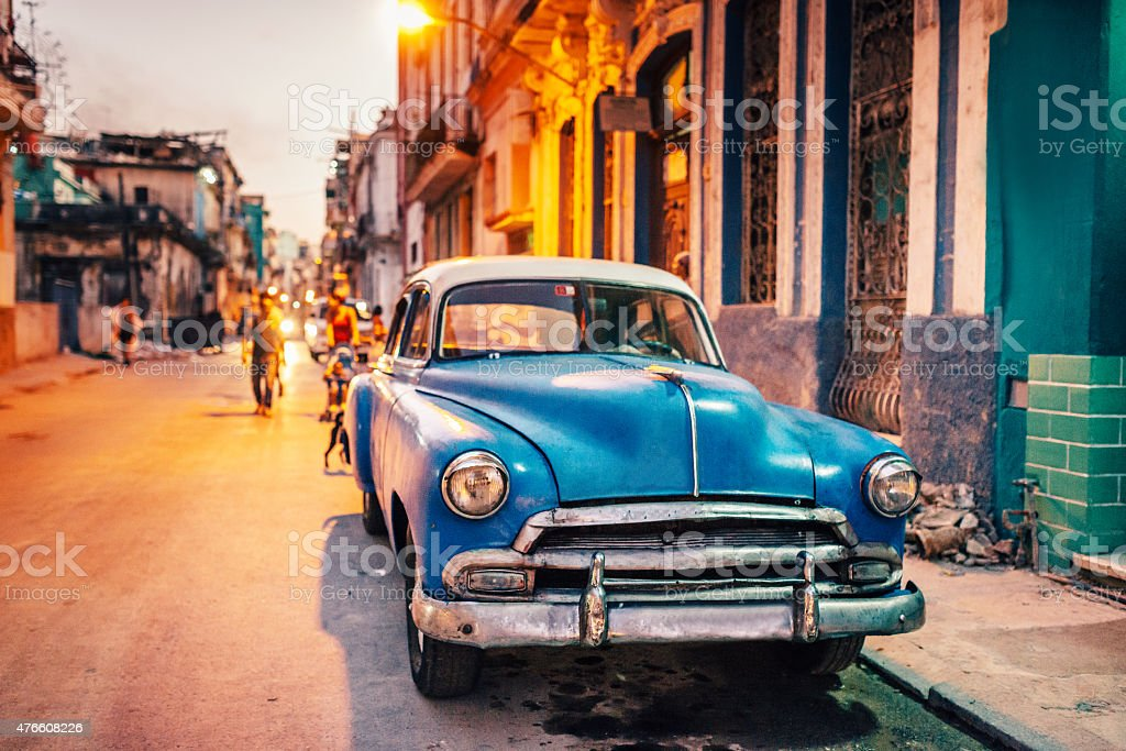 Old American car on street at dusk, Cuba stock photo