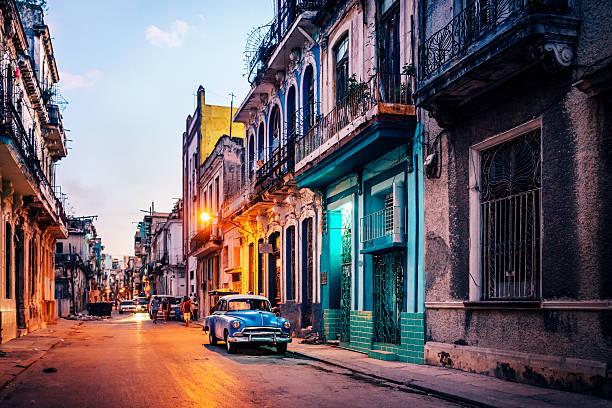 alte amerikanische auto auf straße in der abenddämmerung, havanna, kuba - urlaub in kuba stock-fotos und bilder