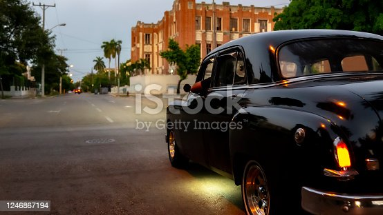 1045032684 istock photo Old American Car on the vibrant streets of Havana, the famous capital of Cuba. Side view with the American flag hanging at the rearview mirror. 1246867194