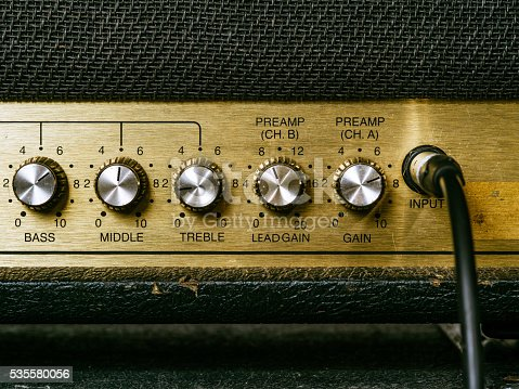 Macro photo of a vintage electric guitar amplifier showing the knobs and input plug..