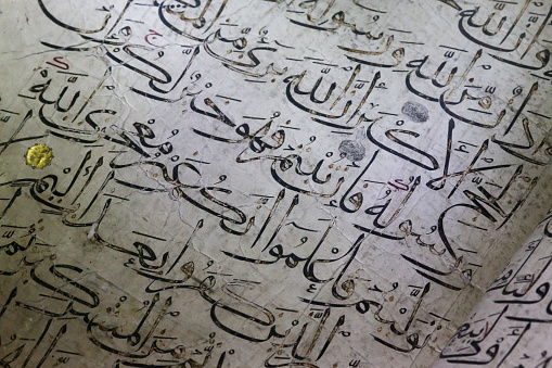 istock Old ancient arabic calligraphy Koran words writings on white paper 676469900