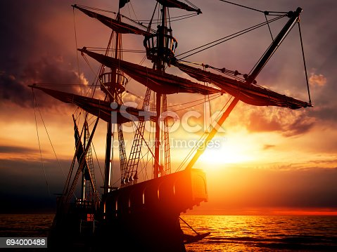 istock Old ancient pirate ship on peaceful ocean at sunset. 694000488
