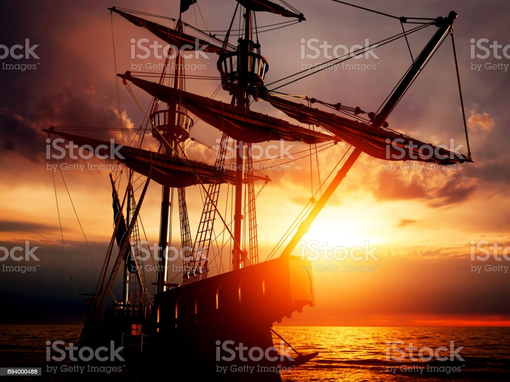 Old ancient pirate ship on peaceful ocean at sunset. stock photo