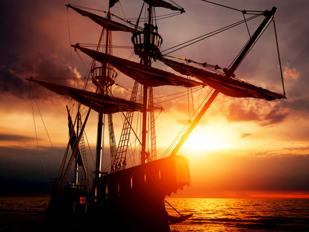 old ancient pirate ship on peaceful ocean at sunset. - vintage nautical stock photos and pictures