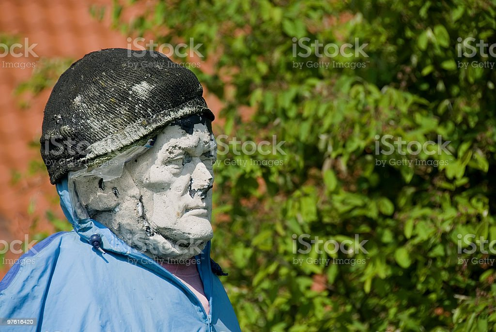 Old ancient stone statue used as a scarecrow 02 royalty-free stock photo