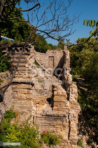 istock Old ancient white destroyed stone house on the green yard with trees around. Poverty and misery, South, summer 1058468558
