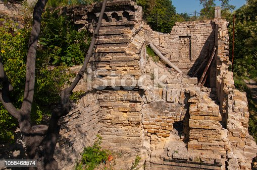 istock Old ancient white destroyed stone house on the green yard with trees around. Poverty and misery, South, summer 1058468574