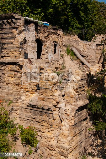 istock Old ancient white destroyed stone house on the green yard with trees around. Poverty and misery, South, summer 1058468576