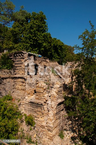 istock Old ancient white destroyed stone house on the green yard with trees around. Poverty and misery, South, summer 1058468580