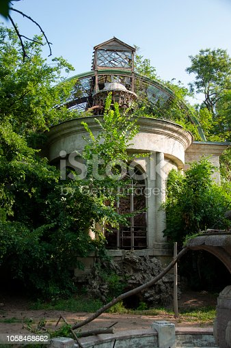istock Old ancient white destroyed stone house on the green yard with trees around. Poverty and misery, South, summer 1058468662