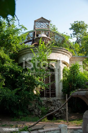 istock Old ancient white destroyed stone house on the green yard with trees around. Poverty and misery, South, summer 1058468672