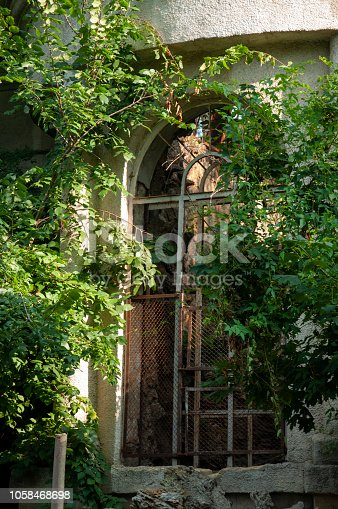 istock Old ancient white destroyed stone house on the green yard with trees around. Poverty and misery, South, summer 1058468698