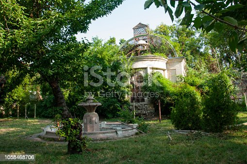 istock Old ancient white destroyed stone house on the green yard with trees around. Poverty and misery, South, summer 1058468706