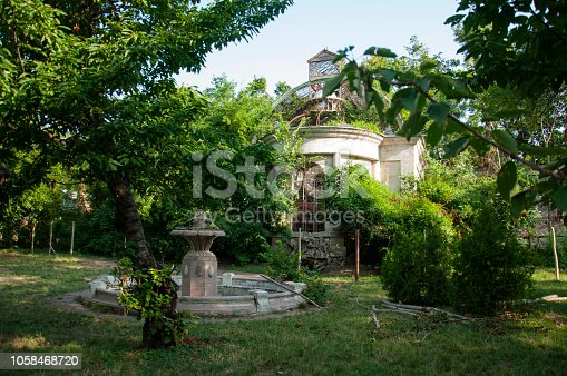 istock Old ancient white destroyed stone house on the green yard with trees around. Poverty and misery, South, summer 1058468720