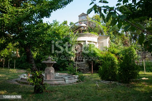 istock Old ancient white destroyed stone house on the green yard with trees around. Poverty and misery, South, summer 1058468766