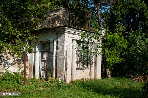 istock Old ancient white destroyed stone house on the green yard with trees around. Poverty and misery, South, summer 1058468778