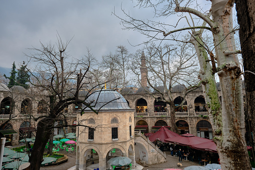 Bursa, Turkey. Old and ancient public house in Bursa (Koza Han) name of coming from silk road center of the city. Architectural details of house and tables and flowers