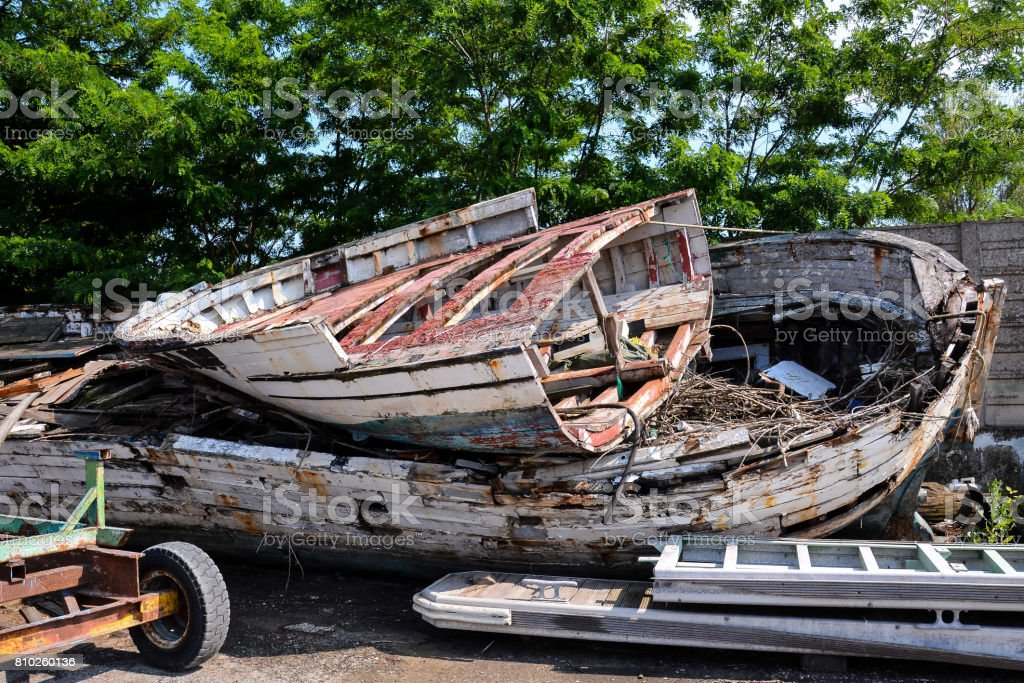 Old and broken wooden boat stranded stock photo