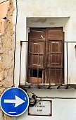 Elche, Alicante, Spain- September 9, 2020: Old and damaged balcony on white facade with blue direction sign in Elche, Alicante, Spain. El Raval neighborhood.