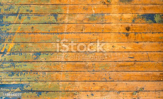 A damaged set of wooden floorboards, with faded blue and green paint.