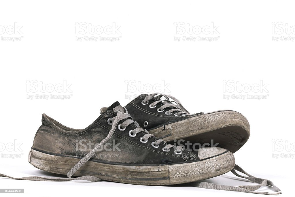 Old and dirty black canvas sneakers, isolated stock photo