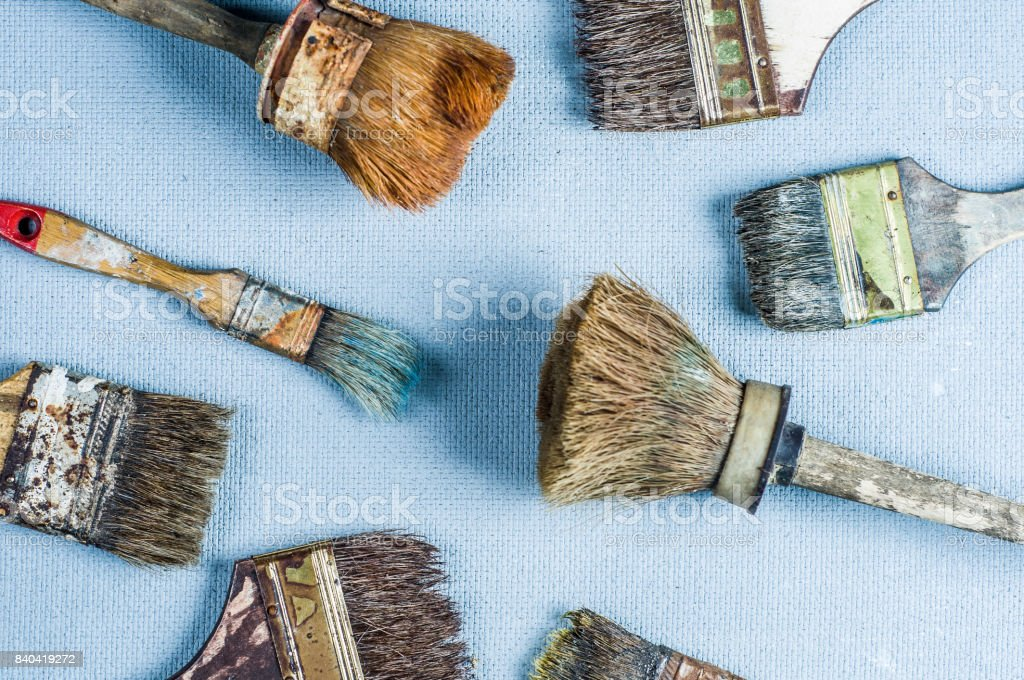 Old and dirty paint brush on a gray background stock photo