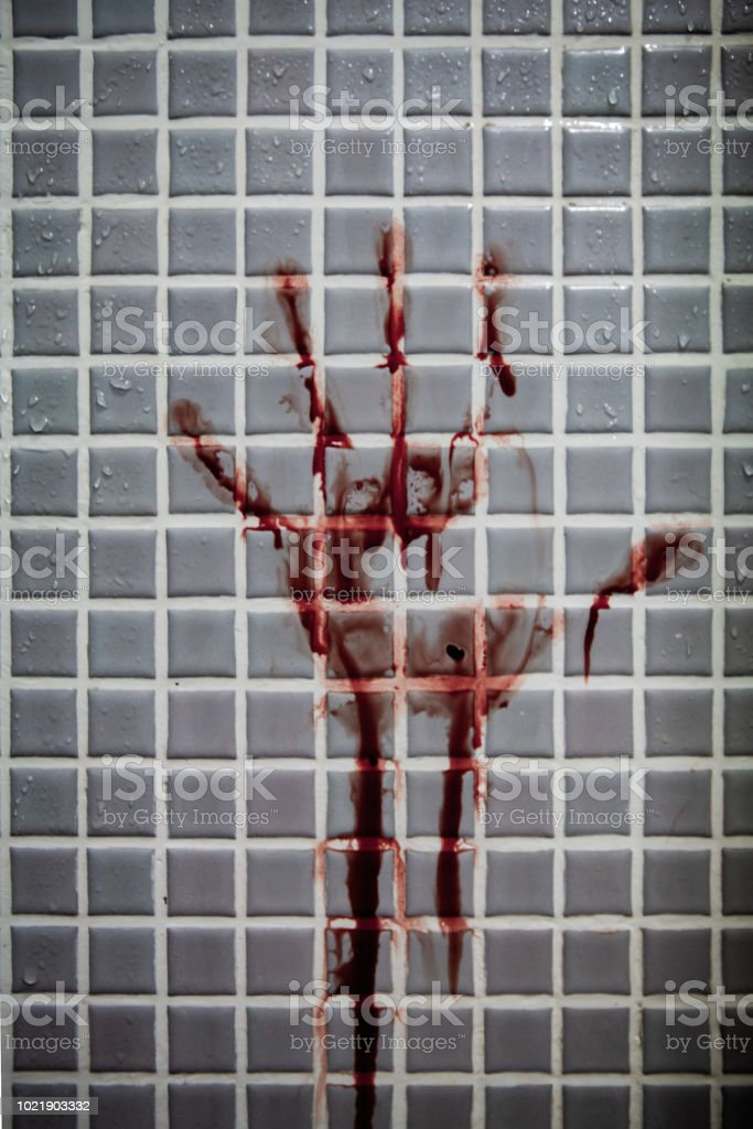 Old and dried out bloody handprint or bloodstains with streaks on wet bathroom tiles wall. stock photo