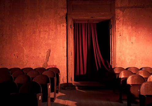 Old and empty dark theater with red curtains