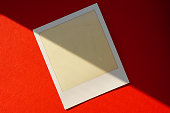 old and empty instant film or photo frame on red background with sunlight