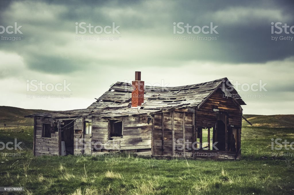 Old and falling down homestead shack on Montana prairie stock photo