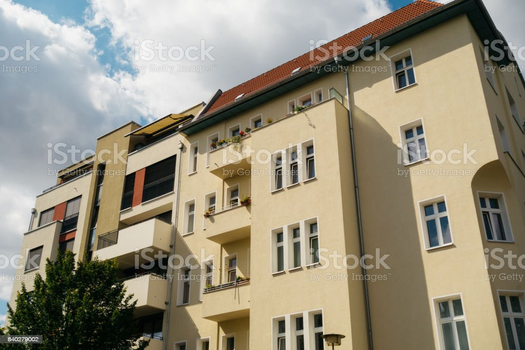 old and modern yellow apartment house stock photo