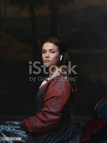 Old and new, concept. Portrait of a girl with a wireless earphone. Beautiful young Renaissance style woman