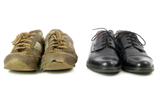 A frontal shot of two pairs of shoes. A very old and used pair and a new shiny pair.
