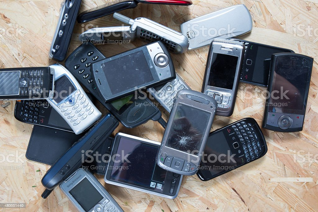 Old and obsolete cellphone on wooden background stock photo