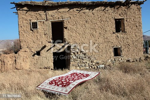 Carpet in front of an anatolian mud cottage