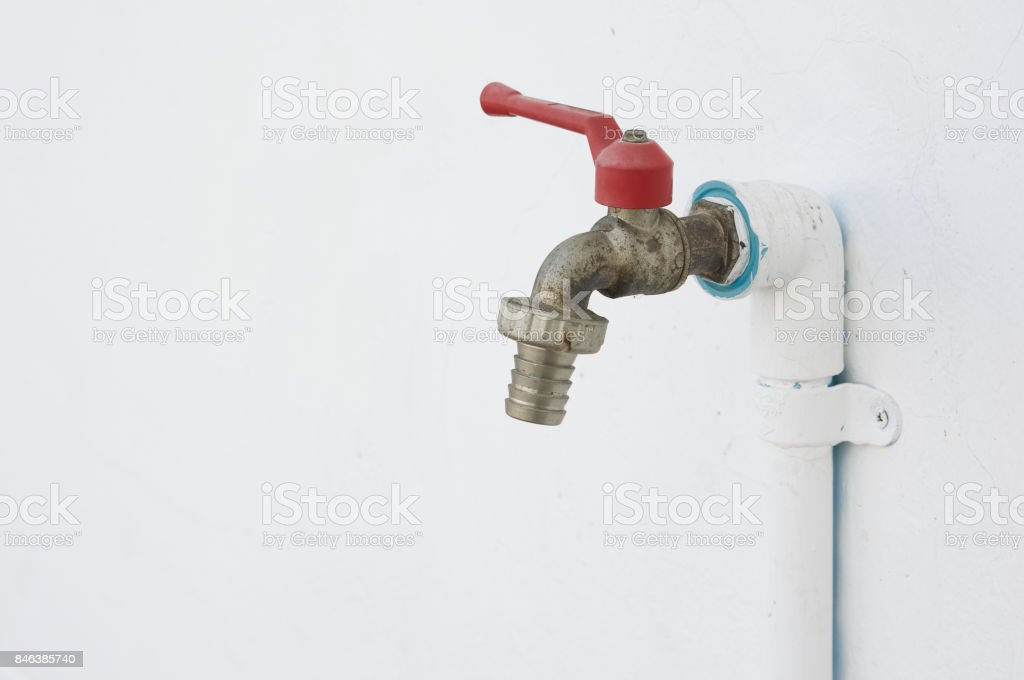 Old and rust chrome faucet with pvc pipeline painted white stock photo