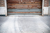 istock Old And Rust Closed Garage With Tire Track Beyond 183538741